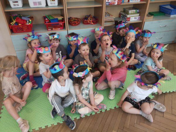 dzieci siedzą na podłodze w opaskach na głowie
