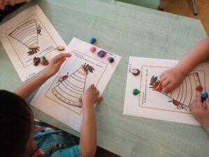 na stole dzieci wyklejają plasteliną tipi