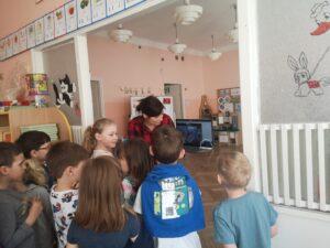 pani pokazuje dzieciom na monitorze dzieci na video rozmowie