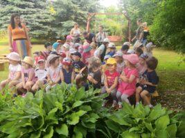 Dzieci siedzą na ławeczkach w ogrodzie