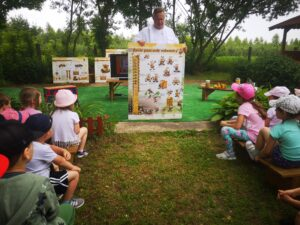 mężczyzna pokazuje dzieciom planszę o pszczołach