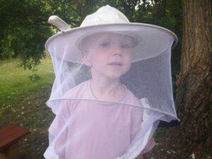 chłopiec ma na głowie kapelusz pszczelarza