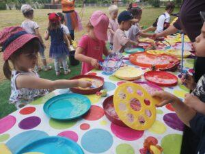 dzieci przy stole puszczają bańki mydlane