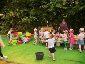 dzieci na zielonej trawie puszczają bańki
