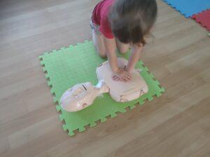 dziewczynka ćwiczy masaż serca na fantomie