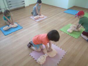 dzieci ćwiczą reanimację na fantomach