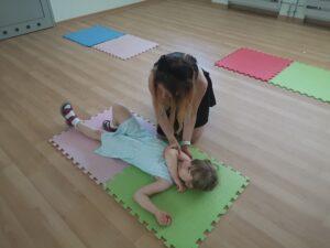 kobieta układa dziewczynkę z pozycji bocznej