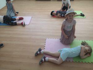dzieci ćwiczą układanie nieprzytomnego w pozycji bocznej