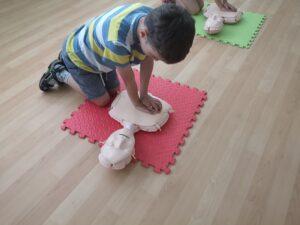 chłopiec wykonuje masaż serca na fantomie