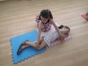 dziewczynka układa koleżankę w pozycji bocznej