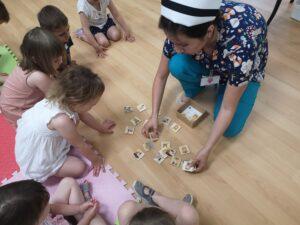 pielęgniarka układa z dziećmi klocki