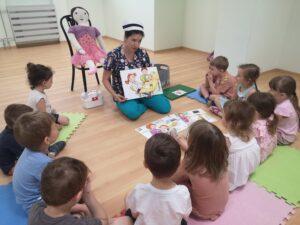 pielęgniarka siedzi i pokazuje dzieciom ilustracje, dzieci siedzą na około