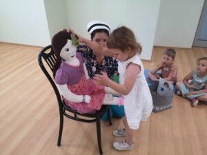 dziewczynka przykłada lalce szkoleniowej okład do czoła