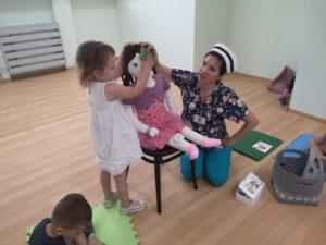 pielęgniarka i dziewczynka stoją przy lalce