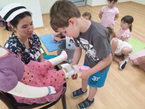 chłopiec zakłada lalce opatrunek na nogę