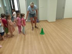 Dzieci stoją jeden za drugim, przed nimi stoi trenerka i tłumaczy zasady wykonywania zadań sportowych. Z przodu przed dziećmi na podłodze stoi zielony pachołek.