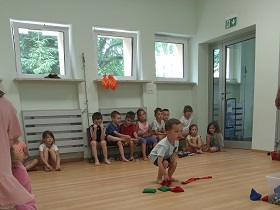 Chłopiec rzuca woreczkim do celu, którym jest przezroczysty pojemnik. Za nim dzieci siedzą na podłodze i na ławeczce.