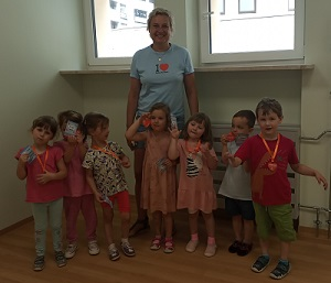 Dzieci z oddziału I Mróweczki stoją obok siebie, na szyi mają zawieszone medale olimpijskie. Za nimi stoi trenerka.