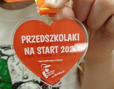 """Medal w kształcie serca, na czerwonym tle napis: Przedszkolaki na start 2021 oraz informacja, że projekt jest współfinansowany przez m.st. Warszawę. Pod napisem znajduje się logo """"Zakochaj sie w Warszawie na Mokotowie"""""""