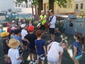 dzieci patrzą na dwóch panów, którzy grają na bębenku oraz gitarze