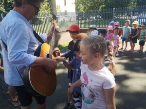dziewczynka obserwuje gitarę