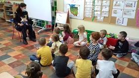 Dzieci siedzą na podłodze zwrócone w stronę Pani strażnik miejskiej. Pani strażnik miejska trzyma w rękach pluszaka rysia.