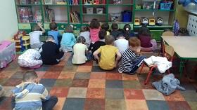 Dzieci siedzą na podłodze z zamkniętymi oczami i odwrócone w stronę szafek.