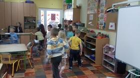 Dzieci szukają pluszaka schowanego w sali.