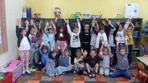 Dzieci stoją i siedzą w sali z uniesionymi rękami do góry. Razem z nimi na podłodze siedzi pluszak Ryś.