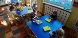 Przy dwóch stolikach siedzą dzieci. Przed każdym dzieckiem stoi żółty pojemnik z kolorowymi papierami. Dzieci przyklejają je do kawałków białego papieru.