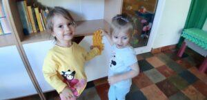 Dwie dziewczynki przykładają żółte klocki do żółtego kawałka papieru.
