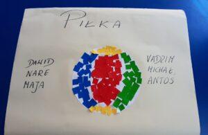 Na kartce A3 wyklejona jest piłka w czterech kolorach: niebieskim, czerwonym, żółtym, zielonym. Na górze kartki jest napis PIŁKA, a po lewej i prawej stronie kartki wypisane są imiona dzieci