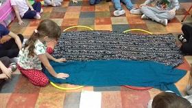 Dzieci siedzą na podłodze wokół obręczy przykrytych chustami. Jedno dziecko dotyka niebieskiej chusty.