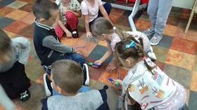 Dzieci siedzą w grupie na podłodze. Układają zero ze skakanki