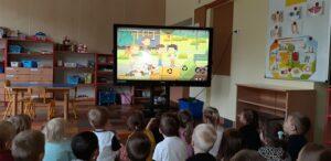 Dzieci siedzą przed ekranem tablicy multimedialnej i oglądają film rysunkowy. Na ekranie widać czworo dzieci , a wokół są pojemniki na śmieci.