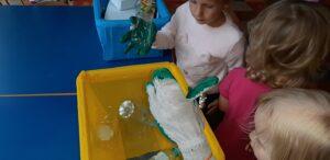 Dziecko wrzuca plastikową butelkę do żółtego pojemnika.