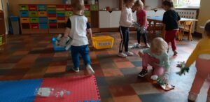 Dzieci chodzą po Sali i zbierają papiery, plastikowe opakowania. Na podłodze ustawione są dwa pojemniki: niebieski z napisem papier oraz żółty z napisem plastik.