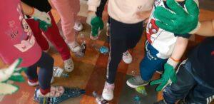 Na podłodze leżą butelki które dzieci zgniatają poprzez stawanie na nich.