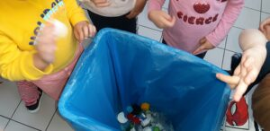 Dzieci stoją wokół pojemnika w którym są plastikowe korki.