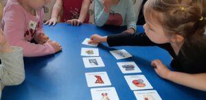 Dzieci siedzą przy stoliku, na blacie ułożone są kartki z rysunkami. Dziewczynka kładzie jeden obrazek.