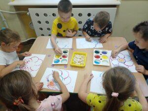 dzieci siedzą przy stoliku i wykonują prace plastyczną
