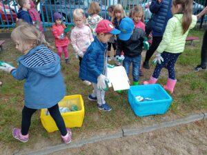 dzieci segregują śmieci do dwóch pojemników