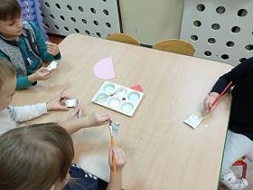 Dzieci siedzą przy stole. Każdy z nich maluje pędzlem kawałek wytłaczanki po jajkach.