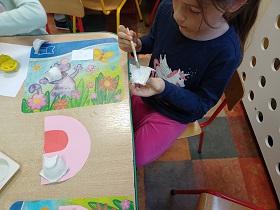 Dziewczynka klei pędzelkiem kawałek zęba. Na stole leży podniebienie z różowej kartki z przyklejonym jednym zębem.