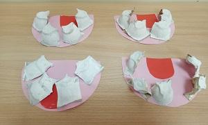 Na stole leżą cztery podniebienia wykonane z różowych kartek z czerwonymi językami i białymi zębami wykonanymi z wytłaczanek po jajkach.