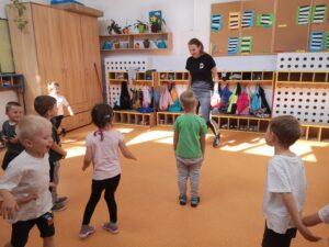 dzieci stoją na przeciwko trenerki i wykonują ćwiczenia