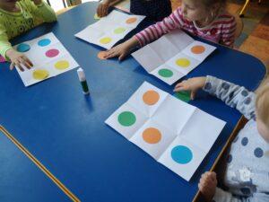 dzieci naklejają kolorowe kropki na karton