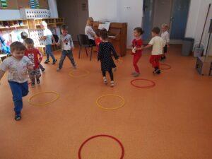 dzieci biegają po sali na około obręczy