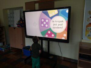chłopiec stoi na przeciwko monitora