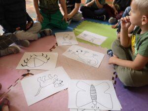dzieci siedzą na podłodze, po środku leżą ilustracje zwierząt